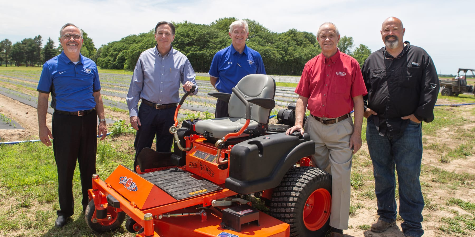 Men pose in field next to large lawnmower